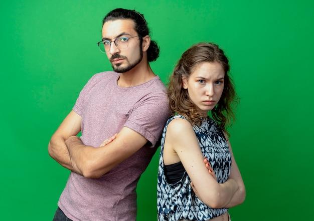 Jong stel man en vrouw fronsen terwijl ze rug aan rug over groene muur staan