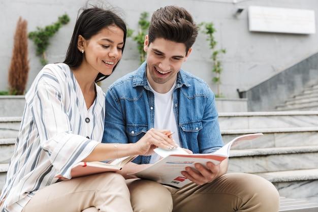 Jong stel man en vrouw in vrijetijdskleding praten en studeren terwijl ze op een bankje in de buurt van trappen buiten zitten