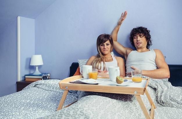 Jong stel met buikpijn na te veel eten in een weekendontbijt op bed thuis