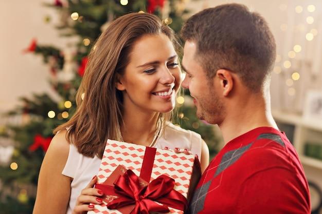 Jong stel met cadeau boven kerstboom