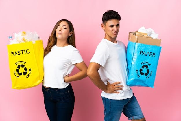 Jong stel met een zak vol plastic en papier op roze die lijden aan rugpijn omdat ze zich hebben ingespannen
