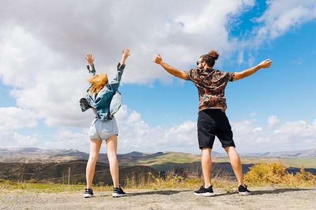 Jong stel met handen omhoog op heuveltop