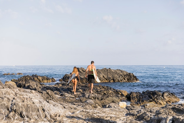 Jong stel met surfplanken lopen op de wal