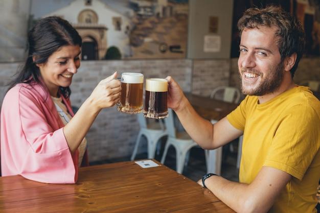 Jong stel op een date die bier roostert in een brouwerijbar-restaurant