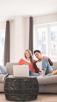 Jong stel op een videogesprek met hun laptop terwijl ze thuis samen op een bank zitten.
