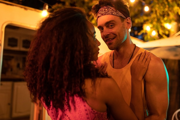 Jong stel op vakantie met de camper. dansen buiten in de nacht. concept over reislustige roadtrips en levensstijl op vakantie