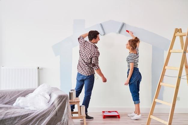 Jong stel schildert de binnenmuur in hun nieuwe appartement