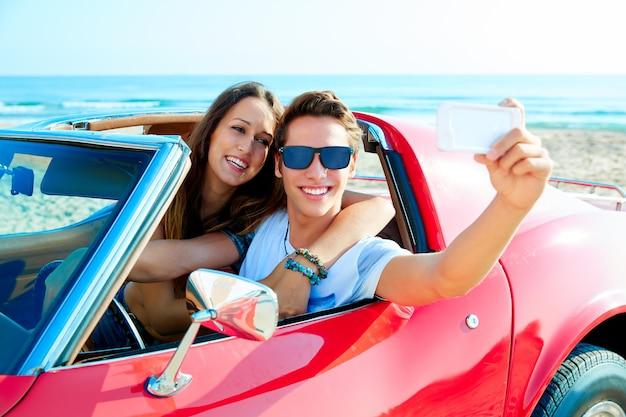 Jong stel selfie blij in res auto op het strand