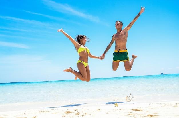 Jong stel springt op het strand op vakantie