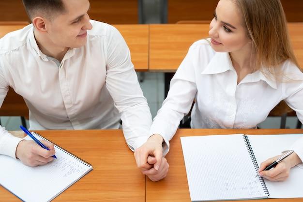 Jong stel studenten, een jongen en een meisje, zitten aan een bureau tijdens een lezing en houden elkaars hand vast.