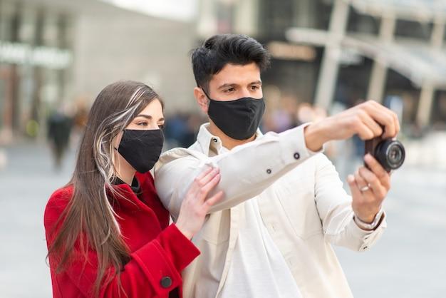 Jong stel toeristen die foto's maken in een stad tijdens covid- of coronaviruspandemie