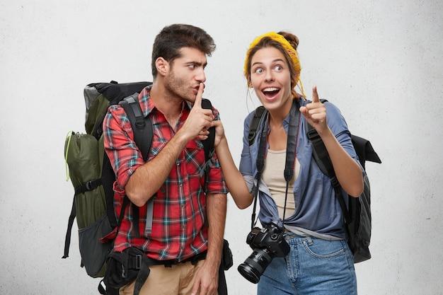 Jong stel van twee wandelaars uitgerust met toeristische accessoires en rugzakken genieten van avontuurlijke reis: bebaarde man maakt shh bord met vinger, vraagt zijn opgewonden vriendin om te zwijgen