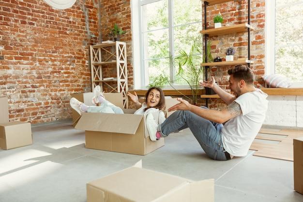 Jong stel verhuisde naar een nieuw huis of appartement. plezier hebben met kartonnen dozen, ontspannen na het schoonmaken en uitpakken op een verhuisdag. kijk gelukkig. familie, verhuizen, relaties, eerste huisconcept.