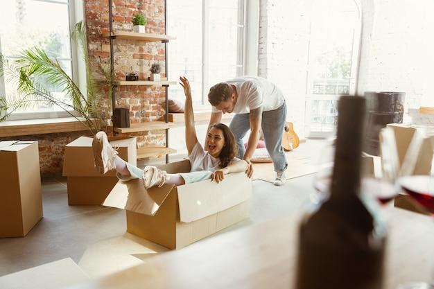 Jong stel verhuisde naar een nieuw huis of appartement. plezier hebben met kartonnen dozen, ontspannen na het schoonmaken en uitpakken op een verhuisdag