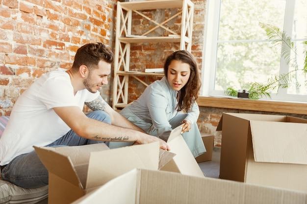 Jong stel verhuisde naar een nieuw huis of appartement. samen kartonnen dozen uitpakken, plezier maken op een verhuisdag