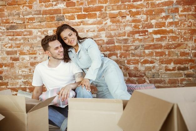 Jong stel verhuisde naar een nieuw huis of appartement. samen liggen, kaddelen, knuffelen, plezier maken op een verhuisdag