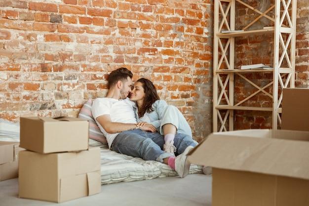 Jong stel verhuisde naar een nieuw huis of appartement. samen liggen, ontspannen na het schoonmaken en uitpakken op een verhuisdag
