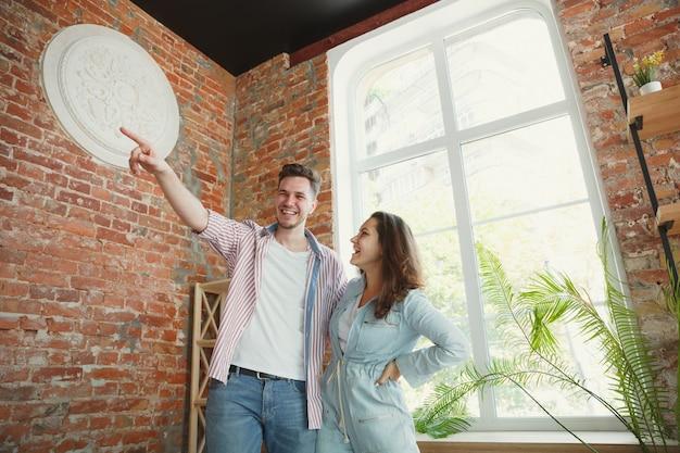 Jong stel verhuisde naar een nieuw huis of appartement. zie er gelukkig en zelfverzekerd uit. familie, verhuizen, relaties, eerste huisconcept. nadenken over toekomstige reparatie en ontspannen na het schoonmaken en uitpakken.