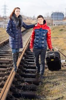 Jong stel wacht op de trein die naast het spoor staat met hun ingepakte koffer met de jonge vrouw balancerend op het metalen spoor met de schouder van de man