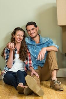Jong stel zat samen op de vloer en lachend in hun nieuwe huis