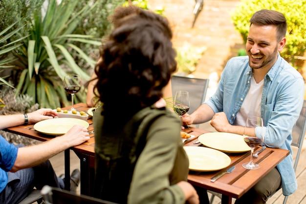 Jong stel zit bij de tafel in de achtertuin
