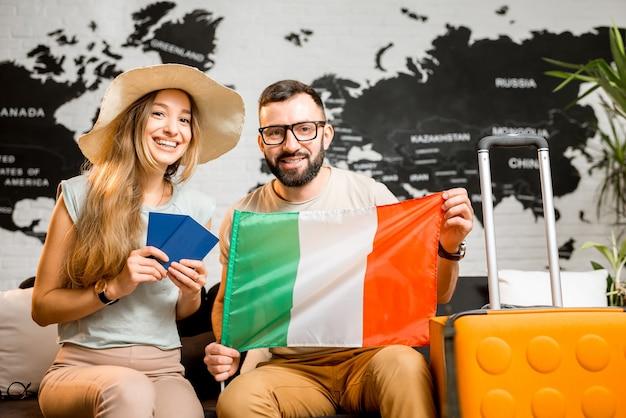 Jong stel zit met italiaanse vlag en paspoorten op het kantoor van het reisbureau op de achtergrond van de wereldkaart en bereidt zich voor op een reis naar italië