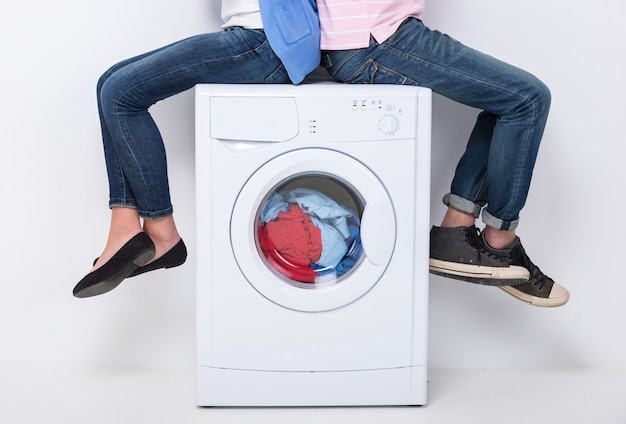 Jong stel zit op de wasmachine.