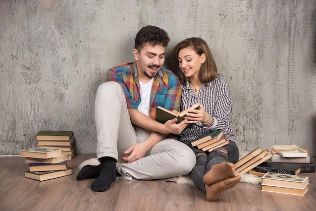 Jong stel zittend op de vloer en het lezen van een boek