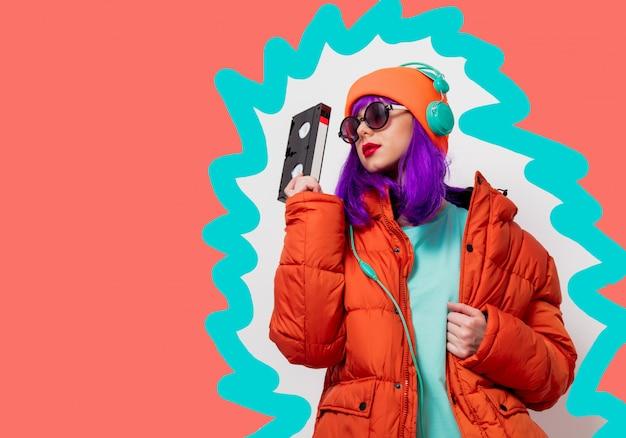 Jong stijlmeisje met vhs-cassette op de getrokken het leven achtergrond van de koraalkleur.