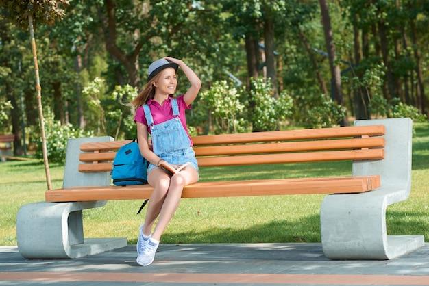 Jong stijlvol gekleed meisje zittend op de bank met een boek?