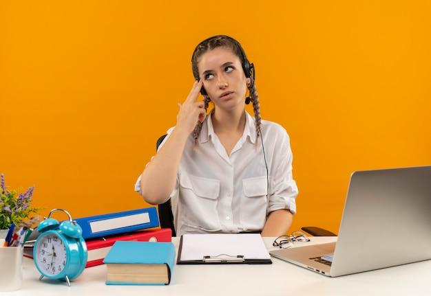 Jong student meisje met vlechten in wit overhemd en koptelefoon met microfoon opzij kijken verbaasd moe en verveeld zitten aan de tafel met laptop mappen klembord en boek over oranje muur