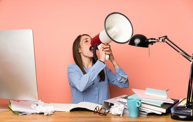Jong studentenmeisje dat door een megafoon schreeuwt