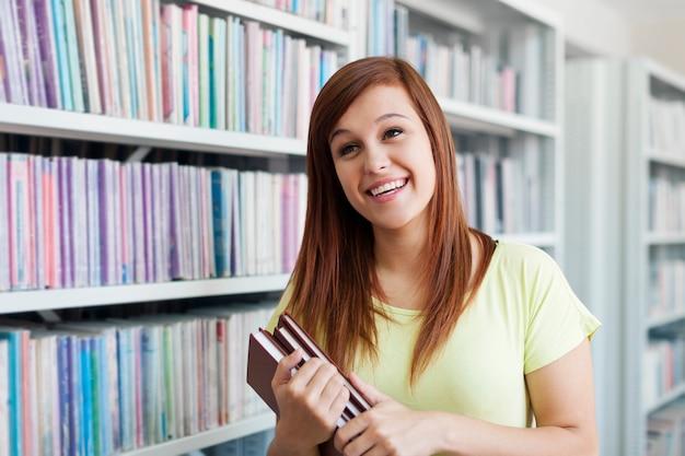 Jong studentenmeisje dat in bibliotheek lacht