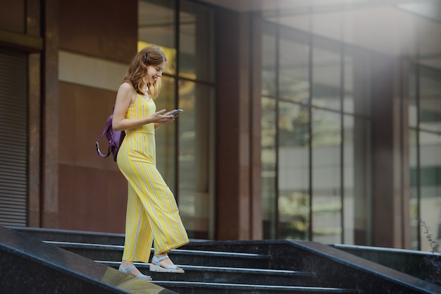 Jong studentenmeisje dat in de campus met haar telefoon, het glimlachen loopt.
