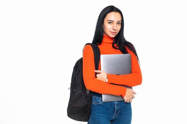 Jong studentenmeisje dat op grijze muur wordt geïsoleerd, die bij camera glimlacht, laptop tegen borst drukt, rugzak draagt, klaar om naar studies te gaan, nieuw project begint en nieuwe ideeën voorstelt.