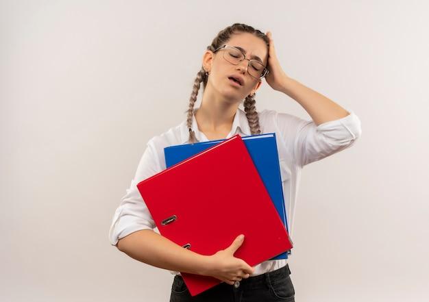Jong studentenmeisje in glazen met vlechten in de mappen van de wit overhemdsholding die moe en overwerkt status over witte muur kijken