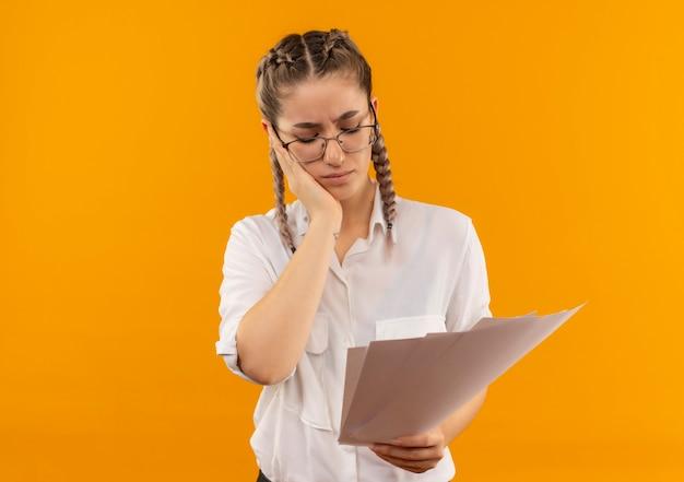 Jong studentenmeisje in glazen met vlechten in wit overhemd die blanco pagina's houden die hen moe en verveeld bekijken die zich over oranje muur bevinden