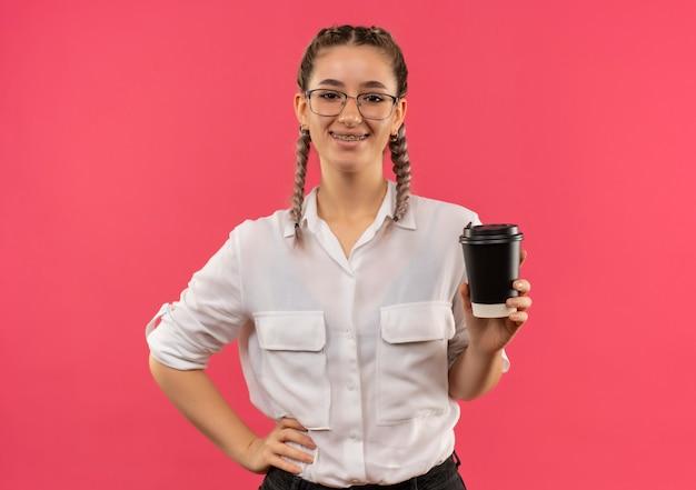 Jong studentenmeisje in glazen met vlechten in wit overhemd met koffiekopje, kijkend naar de voorkant glimlachend zelfverzekerd staande over roze muur