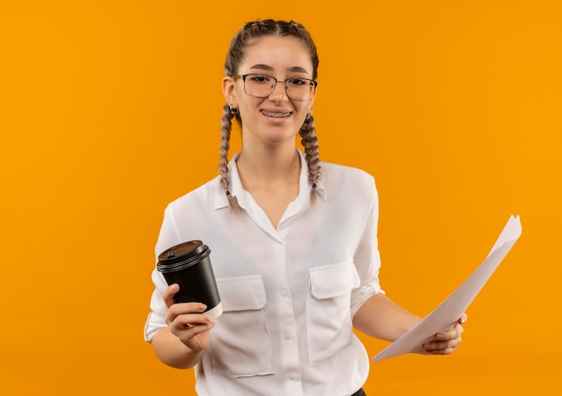 Jong studentenmeisje in glazen met vlechtjes in wit overhemd die koffiekop en blanco pagina's houden die naar voren glimlachend zelfverzekerd over oranje muur kijken