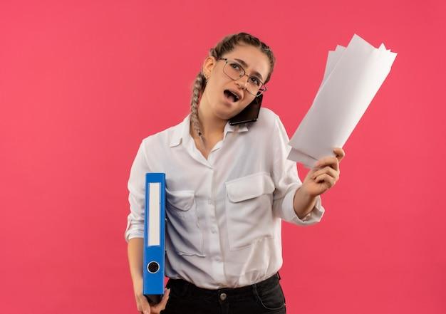 Jong studentenmeisje in glazen met vlechtjes in wit overhemd met map en lege pagina's tijdens het praten op mobiele telefoon en kijkt verbaasd staande over roze muur