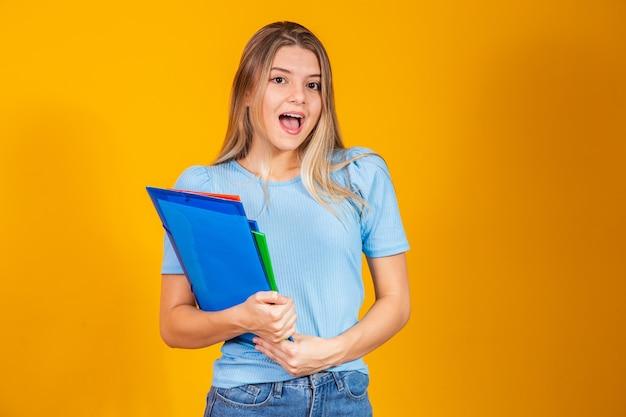 Jong studentenmeisje met boeken op gele achtergrond. terug naar school.