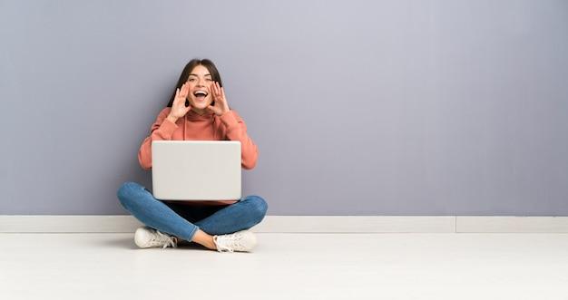 Jong studentenmeisje met laptop op de vloer die met wijd open mond schreeuwt