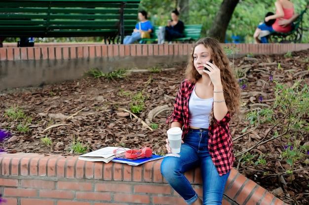 Jong studentenmeisje met mobiele telefoon en koffiekop