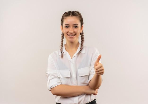 Jong studentenmeisje met vlechten in wit overhemd die aan de voorzijde glimlachen die duimen tonen die omhoog zich over witte muur bevinden
