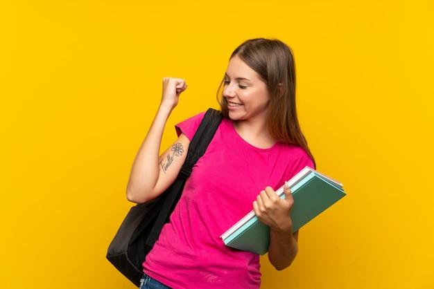Jong studentenmeisje over geïsoleerde gele muur die een overwinning vieren