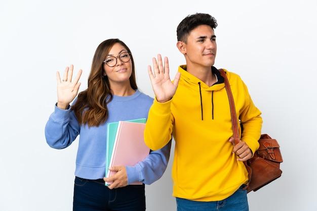 Jong studentenpaar op wit die met hand met gelukkige uitdrukking groeten