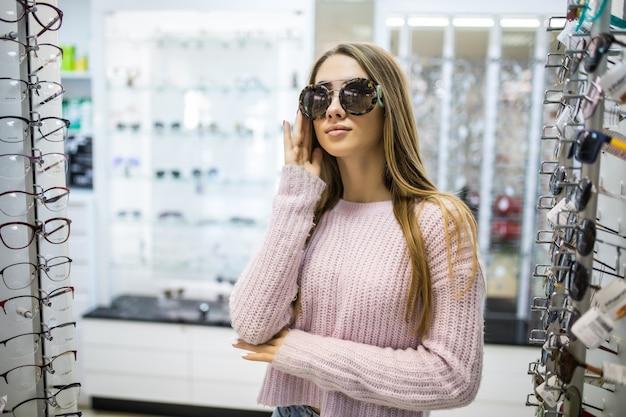 Jong studentmeisje bereidt zich voor op studie en probeert een nieuwe bril voor haar perfecte look in de professionele winkel