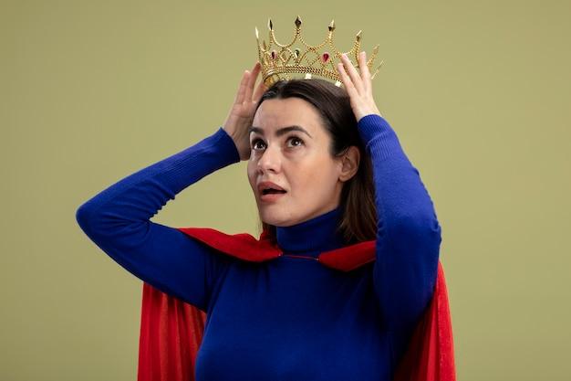 Jong superheldenmeisje die kant bekijken die kroon op hoofd zetten die op olijfgroene achtergrond wordt geïsoleerd