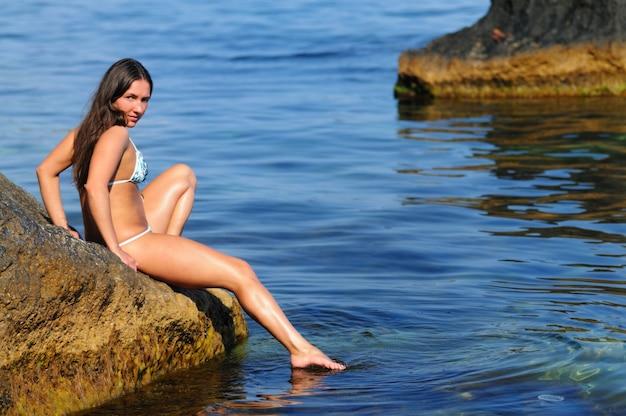 Jong tan meisje die zich voordeed op de zeekust