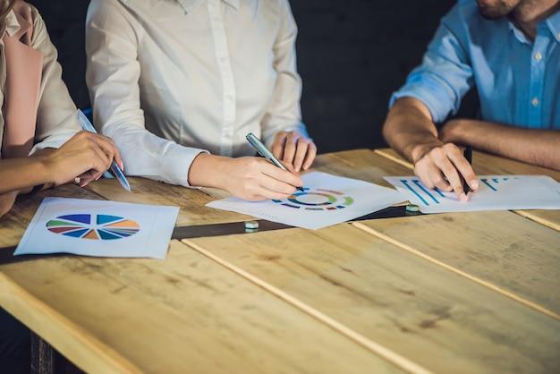 Jong team van collega's die grote vergaderingsbespreking maken in modern teamwerkproces van het bureau van naaiatelier